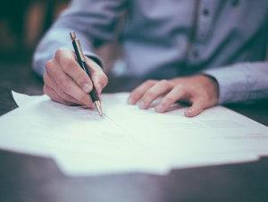 Mano con bolígrafo firmando un documento